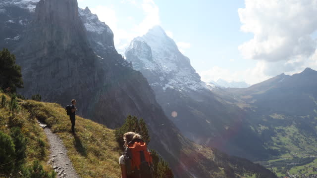 female hiker joins companion on ledge above valley, mountains - junge männer stock-videos und b-roll-filmmaterial