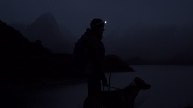 female hiker looking at the landscape at night with a headlight and mountains behind - headlight stock videos & royalty-free footage