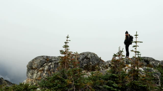 Female hiker looks out at atmospheric view of alpine valley