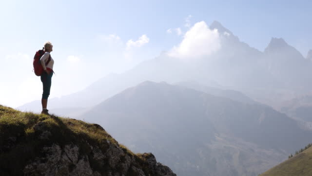 female hiker looks out from mountain ridge, above valley - hand on hip stock videos & royalty-free footage