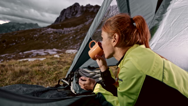 female hiker lying in her tent and drinking tea while admiring the beautiful view of the nearby mountains - tent stock videos and b-roll footage