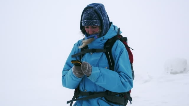 female hiker navigating through snow storm - mitten stock videos & royalty-free footage