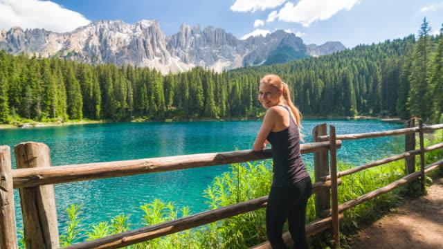 vídeos y material grabado en eventos de stock de mujer caminante sobre senderismo camino a lago de la montaña admirando la vista de las montañas, sonriendo a cámara - austria