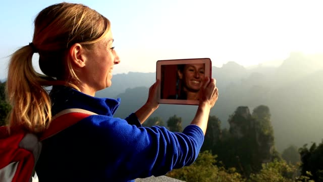 Female hiker on mountain top takes digital tablet picture