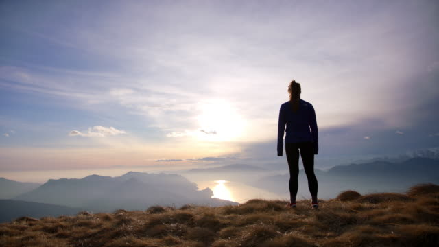 female hiker opens arms in freedom pose on top of mountain looking out towards sunset and lake below - arms outstretched stock videos & royalty-free footage
