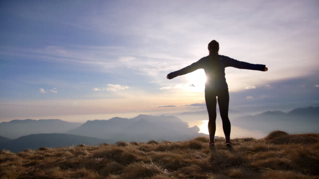 female hiker opens arms in freedom pose on top of mountain looking out towards sunset and lake below - mountain pose stock videos & royalty-free footage
