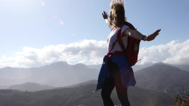 female hiker pauses above mountain valley on windy day - jacket stock videos and b-roll footage