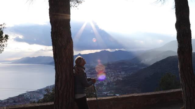 Vrouwelijke wandelaar pauzes boven zee en dorp bij zonsopgang