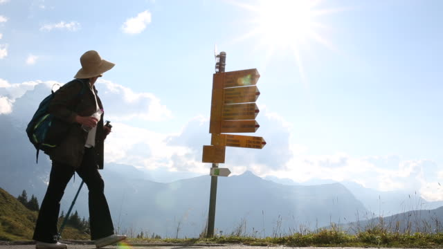 female hiker pauses at signpost, mountains distant - guidance stock videos & royalty-free footage
