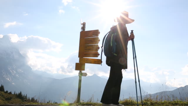 Female hiker pauses at signpost, mountains distant