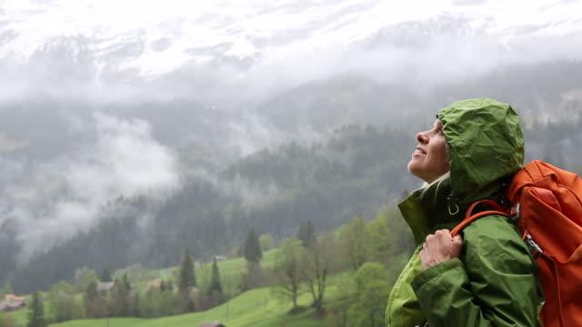 vídeos y material grabado en eventos de stock de female hiker pauses below snow capped mountains, stormy day - brazo humano