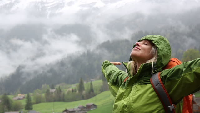Female hiker pauses below snow capped mountains, stormy day