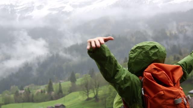 vidéos et rushes de female hiker pauses below snow capped mountains, stormy day - bras humain
