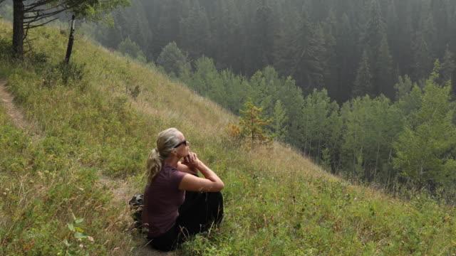 kvinnliga hiker pausar på leden, avkopplande i gräs - endast en medelålders kvinna bildbanksvideor och videomaterial från bakom kulisserna