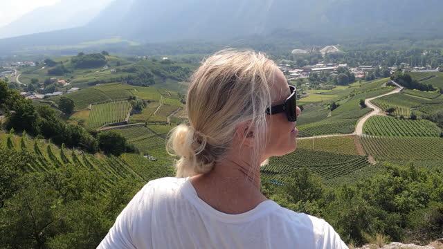 stockvideo's en b-roll-footage met female hiker pauses to enjoy vineyard view - hoofddeksel