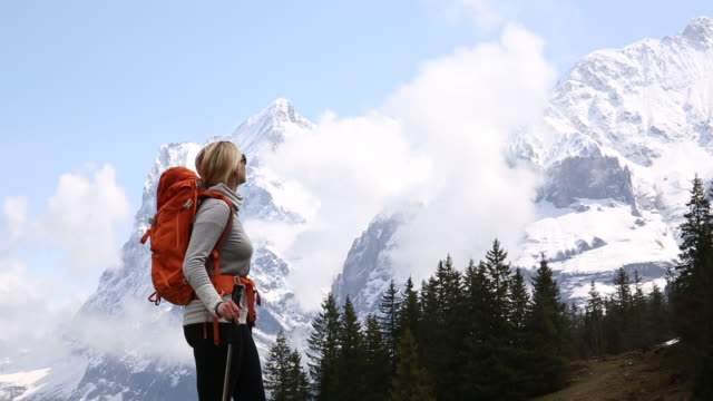 Female hiker pauses while walking below snow capped mountains