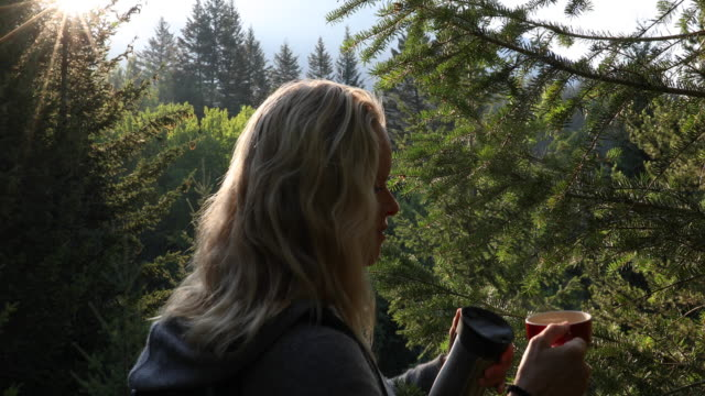 Female hiker pours hot drink in forest, at sunrise