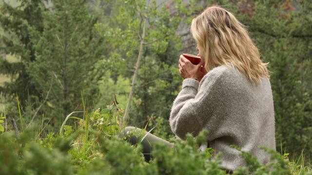 kvinnliga hiker häller varm dryck i muggen, klunkar medan du tittar bort - endast en medelålders kvinna bildbanksvideor och videomaterial från bakom kulisserna