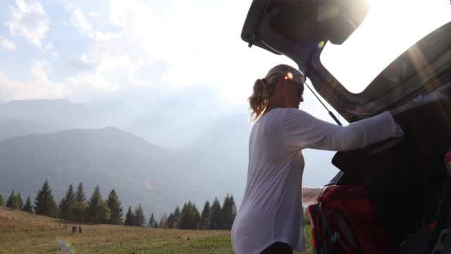 female hiker prepares backpack in car, looks out to mountain scene - 避ける点の映像素材/bロール