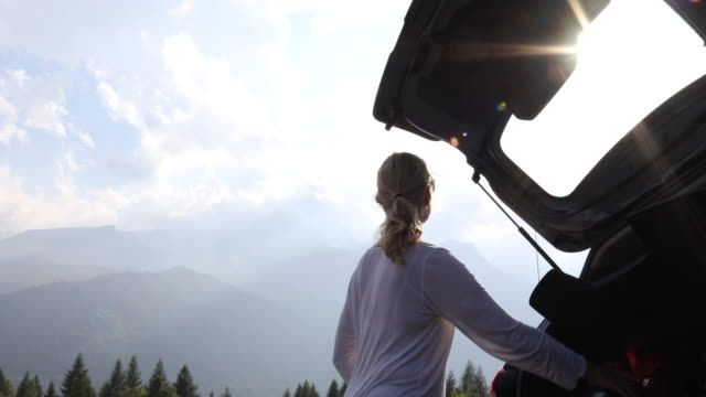 female hiker prepares backpack in car, looks out to mountain scene - boot stock videos & royalty-free footage