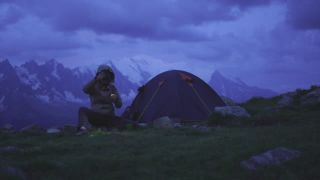 female hiker preparing camp at night in the mountains - tent stock videos & royalty-free footage