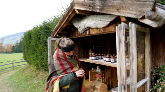 vidéos et rushes de female hiker purchasing local products along mountain trail - châle