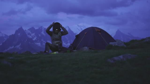 vidéos et rushes de randonneur femelle mettant en place son capot près d'une tente la nuit - lampe frontale
