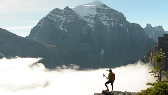 vídeos y material grabado en eventos de stock de female hiker reaches mountain crest above fog, forest - artículo de montañismo