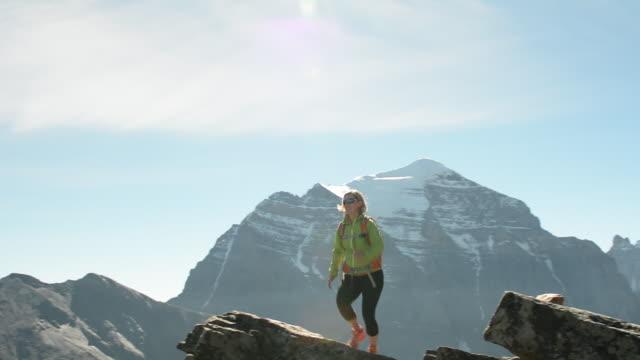 female hiker reaches mountain crest above fog, forest. - oberer teil stock-videos und b-roll-filmmaterial