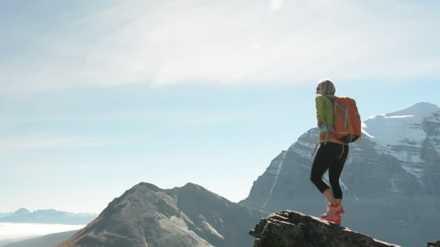 female hiker reaches mountain crest above fog, mountains. - exhilaration stock videos & royalty-free footage