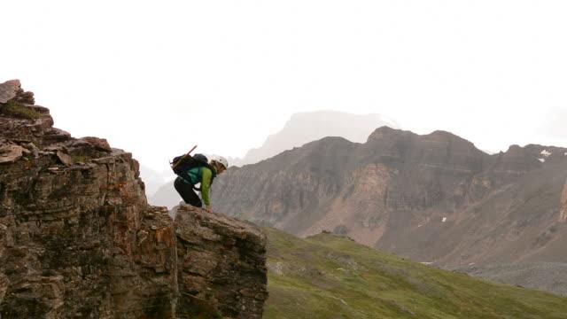 female hiker reaches mountain crest above fog, mountains - braccio umano video stock e b–roll