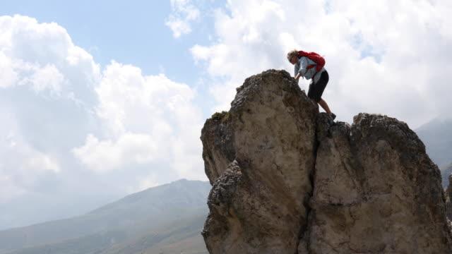 Female hiker reaches pinnacle summit, above valley
