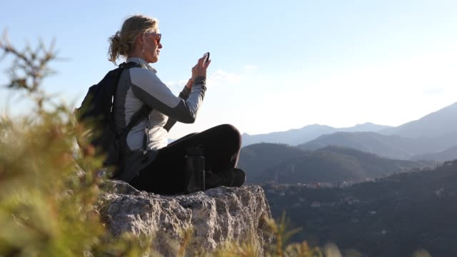 female hiker reaches rock crest above valley, mountains - woman sitting cross legged stock videos & royalty-free footage