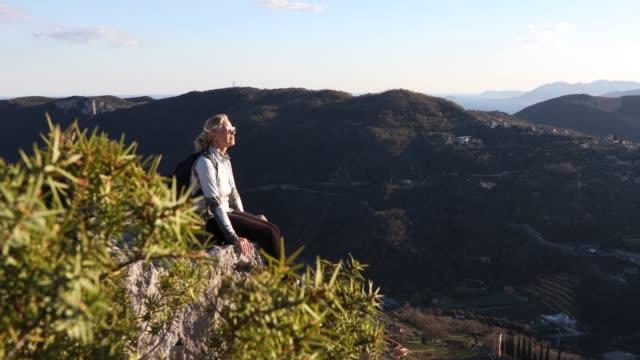 vidéos et rushes de le randonneur féminin atteint la crête de roche au-dessus de vallée, montagnes - admirer le paysage