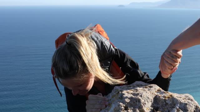 vídeos de stock e filmes b-roll de female hiker receives a helping hand from companion - puxar