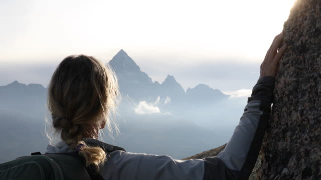 female hiker relaxes above alpine meadow at sunrise - distante video stock e b–roll
