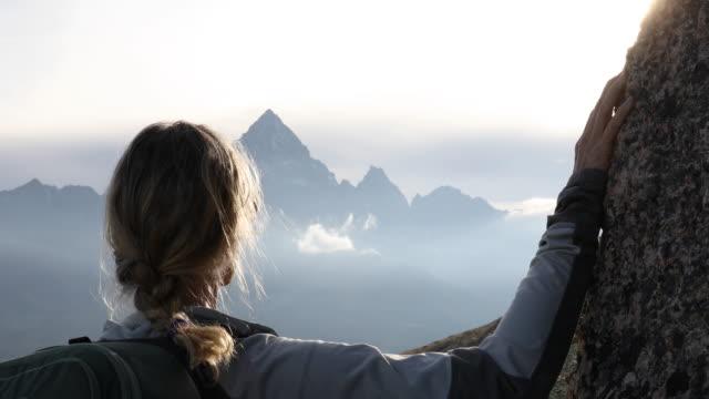 kvinnlig vandrare slappnar över alpina äng vid soluppgången - avlägsen bildbanksvideor och videomaterial från bakom kulisserna