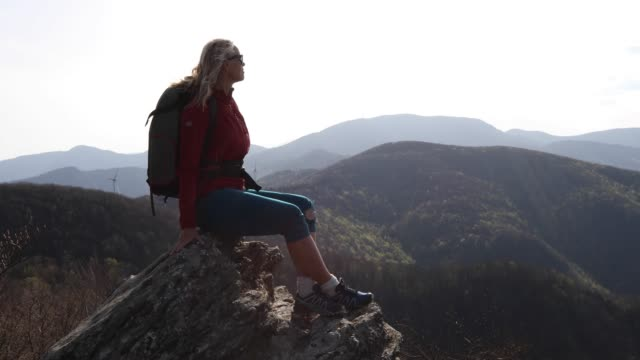 female hiker relaxes above mountains at sunrise - legs crossed at ankle stock videos & royalty-free footage