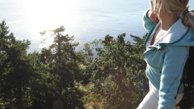 female hiker relaxes above ocean landscape - one mature woman only stock videos & royalty-free footage