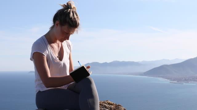 vidéos et rushes de randonneur féminin détend au-dessus de la mer et de la vallée au lever du soleil - carnet