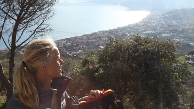 female hiker relaxes above sea and village at sunrise - down jacket stock videos and b-roll footage