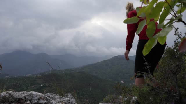 female hiker relaxes above valley and mountains on stormy day - gambe incrociate video stock e b–roll