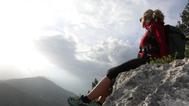 female hiker relaxes above valley and mountains on stormy day - legs crossed at ankle stock videos and b-roll footage