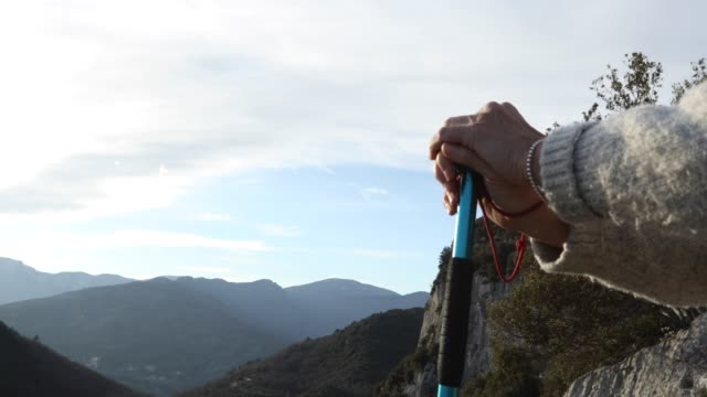 female hiker relaxes above valley at sunrise - hiking pole stock videos and b-roll footage