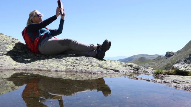Female hiker relaxes by mountain pond with digital tablet