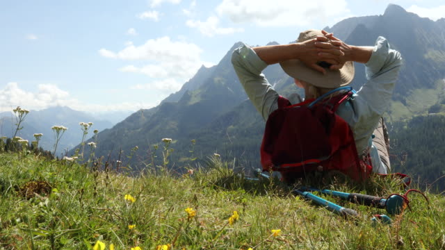 Female hiker relaxes in alpine meadow, looks towards mountains