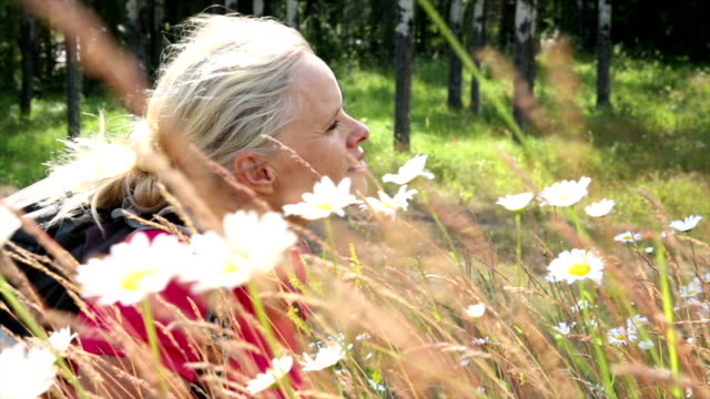 Female hiker relaxes in field of daisies