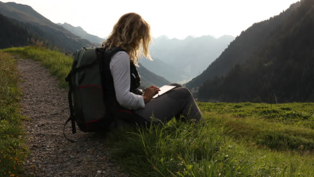 vidéos et rushes de female hiker relaxes in mountain meadow with digital tablet - montrer la voie
