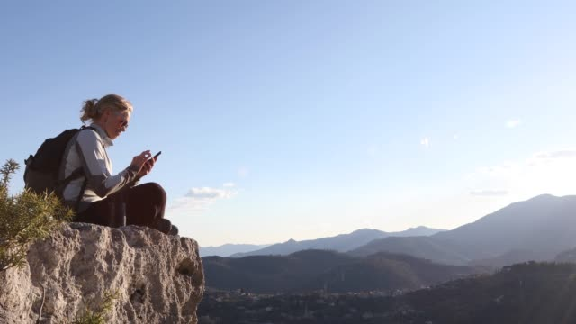 female hiker relaxes on cliff edge, send text and takes pic - photographing stock videos & royalty-free footage