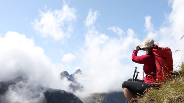 female hiker relaxes on high mountain slope, takes phone pic - rucksack stock videos & royalty-free footage